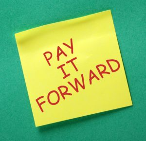 The phrase Pay It Forward in red text on a yellow sticky note posted on a green notice board
