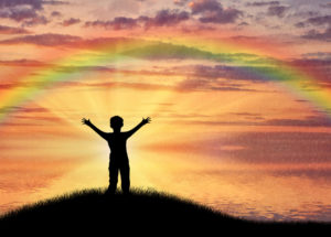 Happy child standing beside sea on hill sunset sky and rainbow. Childhood concept